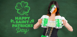 Composite image of irish girl with beer. Irish girl with beer against green chalkboard Royalty Free Stock Photos