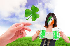 Composite image of irish girl with beer. Irish girl with beer against green field Stock Photo