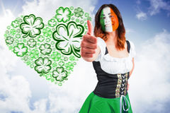 Composite image of irish girl showing thumbs up. Irish girl showing thumbs up against bright blue sky with clouds Stock Photo