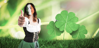Composite image of irish girl showing thumbs up. Irish girl showing thumbs up against dew on the grass close up Royalty Free Stock Photos