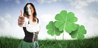 Composite image of irish girl showing thumbs up. Irish girl showing thumbs up against field of grass under blue sky Stock Photography