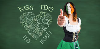 Composite image of irish girl showing thumbs up. Irish girl showing thumbs up against green chalkboard Royalty Free Stock Photos