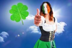 Composite image of irish girl showing thumbs up. Irish girl showing thumbs up against sky Stock Image