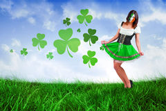 Composite image of irish girl smiling. Irish girl smiling against field of grass under blue sky Royalty Free Stock Photos