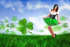 Composite image of irish girl smiling. Irish girl smiling against field of grass under blue sky Stock Photo