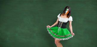 Composite image of irish girl smiling. Irish girl smiling against green chalkboard Stock Photo