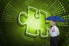 Composite image of jigsaw piece and businessman holding umbrella Stock Photo