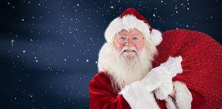 Composite image of jolly santa carries his sack Stock Image