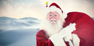 Composite image of jolly santa carries his sack Royalty Free Stock Photography
