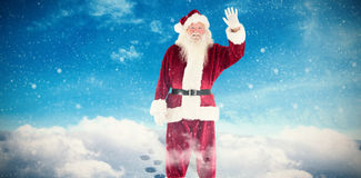 Composite image of jolly santa waving at camera Royalty Free Stock Photo