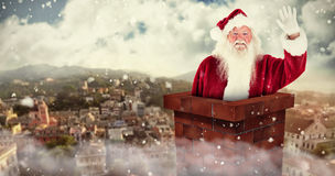 Composite image of jolly santa waving at camera. 3D Jolly Santa waving at camera against city landscape Stock Photography