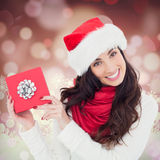 Composite image of joyful brunette presenting christmas gift Royalty Free Stock Photography