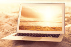 Composite image of laptop kept on sand Royalty Free Stock Images