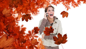 Composite image of laughing cute brunette in winter fashion phoning Royalty Free Stock Image