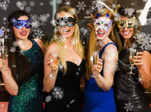 Composite image of laughing friends wearing masks holding champagne glasses Royalty Free Stock Images