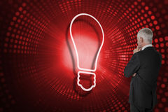 Composite image of light bulb and businessman looking Stock Photography