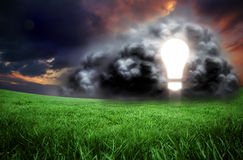 Composite image of light bulb in cloud. Against green field under orange sky Royalty Free Stock Photos
