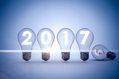 Composite image of light bulbs with 2017 over white background. Light bulbs with 2017 over white background against grey vignette Royalty Free Stock Images