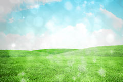 Composite image of light design shimmering on green. Light design shimmering on green against field and sky Royalty Free Stock Photos
