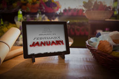 Composite image of list of months. List of months against digital tablet on table royalty free stock image