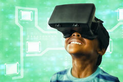 Composite image of little boy holding virtual glasses and looking away Stock Images