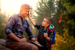 Composite image of a little boy showing magnifying glass to his father Stock Photo