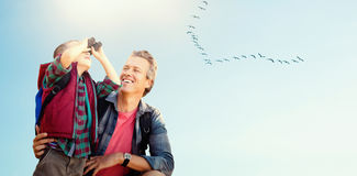 Composite image of little boy using binocular with his father. Little boy using binocular with his father  against flock of bird flying over field Royalty Free Stock Photos
