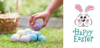 Composite image of little girl collecting easter eggs Stock Photo