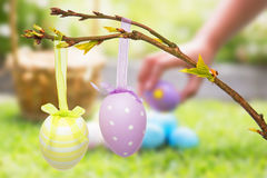 Composite image of little girl collecting easter eggs Stock Images