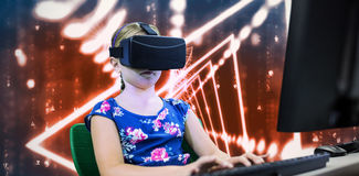 Composite image of little girl holding virtual glasses front of her computer. Little girl holding virtual glasses front of her computer against abstract Stock Photo