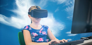 Composite image of little girl holding virtual glasses front of her computer. Little girl holding virtual glasses front of her computer against blue sky with Royalty Free Stock Images