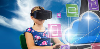 Composite image of little girl holding virtual glasses front of her computer. Little girl holding virtual glasses front of her computer against blue sky with Royalty Free Stock Photography