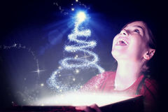 Composite image of little girl opening a magical christmas gift. Little girl opening a magical christmas gift against christmas tree design Royalty Free Stock Photos