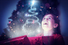 Composite image of little girl opening a magical christmas gift Royalty Free Stock Photos