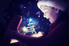 Composite image of little girl opening a magical christmas gift Royalty Free Stock Photography