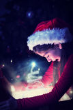 Composite image of little girl opening a magical christmas gift Royalty Free Stock Images