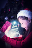 Composite image of little girl opening a magical christmas gift Stock Image
