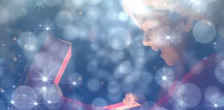 Composite image of little girl opening a magical christmas gift stock photos