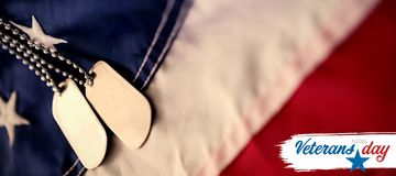 Composite image of logo for veterans day in america. Logo for veterans day in america  against close-up of dog tag chains on flag Royalty Free Stock Photography