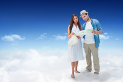 Composite image of lost hipster couple looking at map. Lost hipster couple looking at map against bright blue sky over clouds Royalty Free Stock Photos