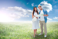 Composite image of lost hipster couple looking at map Stock Photos