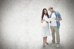 Composite image of lost hipster couple looking at map Royalty Free Stock Photography