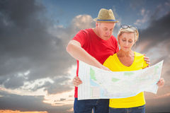 Composite image of lost tourist couple using map. Lost tourist couple using map against blue and orange sky with clouds Royalty Free Stock Images