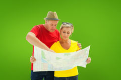 Composite image of lost tourist couple using map. Lost tourist couple using map against green vignette Royalty Free Stock Image
