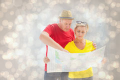 Composite image of lost tourist couple using map. Lost tourist couple using map against light glowing dots design pattern Stock Photo