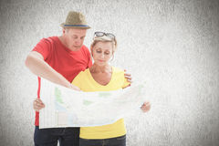 Composite image of lost tourist couple using map. Lost tourist couple using map against white background Royalty Free Stock Photography