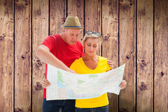 Composite image of lost tourist couple using map. Lost tourist couple using map against wooden planks background Royalty Free Stock Photography