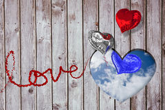 Composite image of love spelled out in petals. Love spelled out in petals against bright blue sky with clouds Stock Image