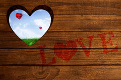Composite image of love spelled out in petals. Love spelled out in petals against field of grass under blue sky Stock Image