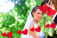 Composite image of loving bride and groom in garden. Loving bride and groom in garden against hearts hanging on a line Royalty Free Stock Photo